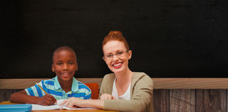 Composite image of happy pupil and teacher. Happy pupil and teacher against blackboard on wooden wall Royalty Free Stock Photography