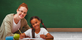 Composite image of happy pupil and teacher. Happy pupil and teacher against greenboard on wall in school Stock Images