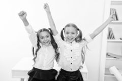 Happy pupils keep hands up in school classroom, victory concept. Little girls celebrate victory. We are the winners. Happy little girls stock photography