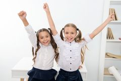 Happy pupils keep hands up in school classroom, victory concept. Little girls celebrate victory. We are the winners. Happy little girls stock photo