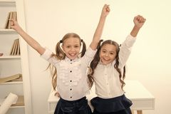 Happy pupils keep hands up in school classroom, victory concept. Little girls celebrate victory. We are the winners. Happy little girls stock image