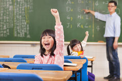 Happy pupils raising hands during the lesson Stock Photos