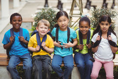 Happy pupils with schoolbags sitting on bench Stock Images