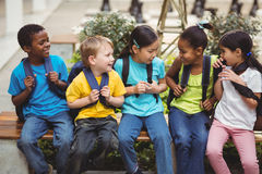 Happy pupils with schoolbags sitting on bench Royalty Free Stock Image
