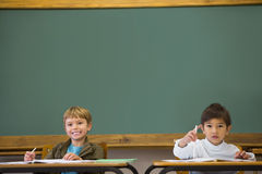 Happy pupils writing in notepad at desks Royalty Free Stock Image