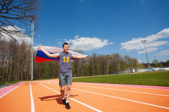 Happy race winner waving Russian flag on the track. Portrait of teenage athlete, running with flag of Russian Federation outside on the racetrack Stock Images