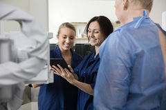 Happy Radiologists Using Tablet Computer While Standing By Patie Royalty Free Stock Images