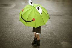 Happy rain. Child standing in rain with happy face umbrella royalty free stock images