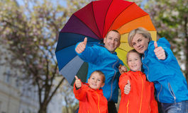 Happy rain family show thumbs up. Family show thrumbs up  under umbrella in rainy day Royalty Free Stock Photography