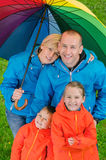 Happy rain family  under colorful umbrella. Top view Stock Photo