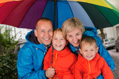 Happy rain family under umbrella. Colorful family smiling in the rainy day under umbrella Stock Photos