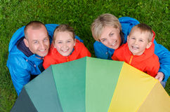 Happy rain family unter umbrella top view. Portrait happy and colorful family  in rainy day top view Royalty Free Stock Images