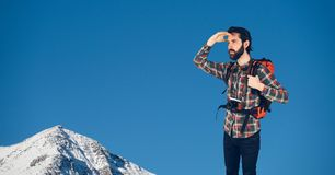 Happy rambler looking far away in front of snow-covered mountains with blue sky Royalty Free Stock Photography