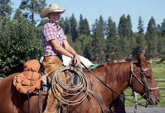 Happy Rancher. Beautiful blond cowgirl happy to be riding her horse royalty free stock photography