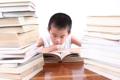 Happy reading. Chinese boy reading between two pile of books stock photography
