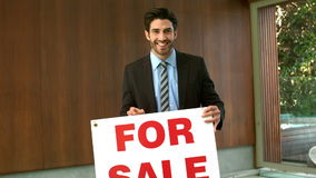 Happy real estate agent with sold sign. In front of house