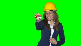 Happy realtor girl with yellow helmet on head and new house keys in hand. Smiling real estate agent isolated on green even chroma key background. Static stock footage