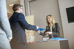 Happy receptionist giving file to businessman at convention center stock photo