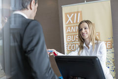 Happy receptionist giving identity card to businessman at convention center stock image