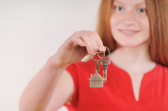 Happy red hair girl hold and offer house key Royalty Free Stock Photo