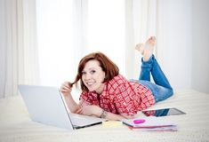 Happy red hair student, business woman lying down working on laptop Royalty Free Stock Images