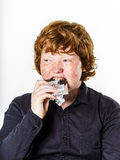 Happy red-haired boy with chocolate bar Royalty Free Stock Photography