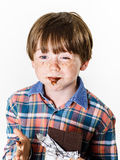 Happy red-haired boy with chocolate bar Stock Image