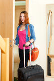 Happy red-haired cute girl with luggage loocking door lock and l Royalty Free Stock Images