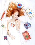 Happy red-haired girl in bed with Christmas gifts. Stock Photos