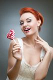 Happy red-haired girl holding candy Stock Images
