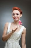 Happy red-haired girl holding candy Royalty Free Stock Photo