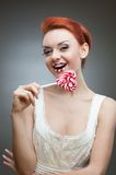 Happy red-haired girl holding candy Stock Photo
