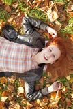 Happy red-haired girl at the park in autumn. Royalty Free Stock Image