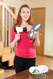 Happy red-haired girl warming shoes with hairdryer Stock Photography