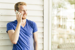 Happy red haired handsome man using phone and smiling Royalty Free Stock Photography