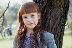 Happy red-haired little girl leaned against a tree Royalty Free Stock Photography
