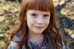 Happy red-haired little girl outdoors Royalty Free Stock Image