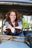 Happy red haired woman on a tractor Royalty Free Stock Photography