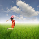 Happy red woman jumping in green rice fields and clouds sky. Summer holiday concept Stock Images