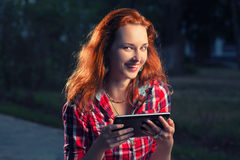 Happy redhair girl with digital tablet in hands posing outdoors, casual modern life Stock Photo
