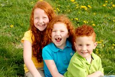 Happy redhead children. A portrait of three cute red headed children smiling outdoors Stock Image