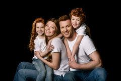 Happy redhead family sitting embracing and smiling at camera Stock Photo