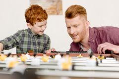 Happy redhead father and son playing table football together at home royalty free stock photo