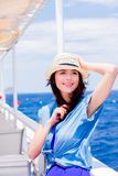 Girl in blue dress and hat have a voyage on a boat. Happy redhead girl in blue dress and hat have a voyage on a boat in Greece. Summertime vacation concept Stock Photography