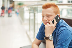 A happy redhead man with freckles wearing casual blue T-shirt and elegant watch having rest in shopping mall communicating with hi Stock Images