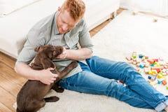 Happy redhead man playing with labrador retriever puppy Royalty Free Stock Photos