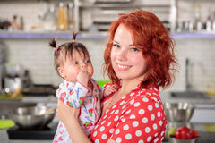 Happy redhead mother with little doughter on hands royalty free stock photography