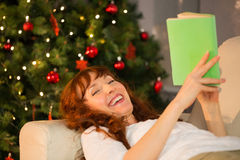 Happy redhead reading on the couch at christmas Stock Image