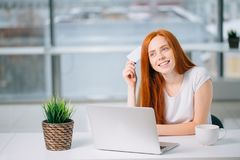 Happy redhead shopper deciding what to buy on line holding a credit card sitting.  Royalty Free Stock Photos