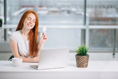 Happy redhead shopper deciding what to buy on line holding a credit card sitting stock photo